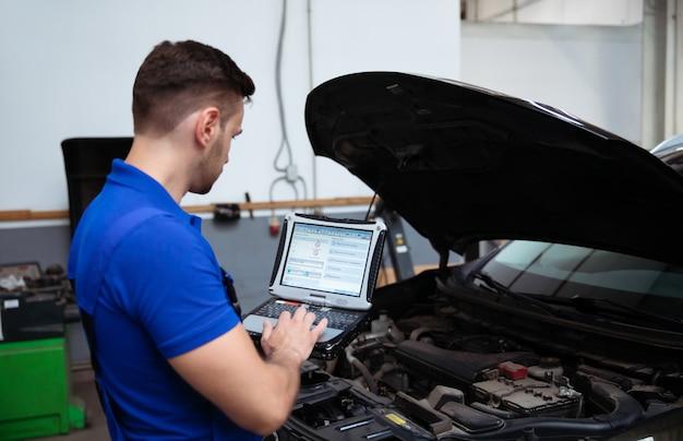 Junger selbstbewusster, gutaussehender automechaniker mit laptop in der hand führt computerdiagnosen für fehler in den autosystemen durch