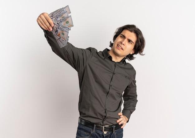 Junger selbstbewusster gutaussehender kaukasischer mann hält und schaut auf geld