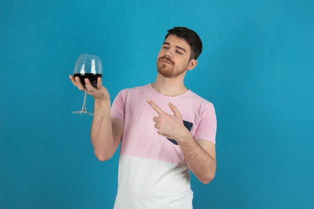 Junger selbstbewusster, gutaussehender kerl, der mit dem finger auf ein glas wein zeigt.