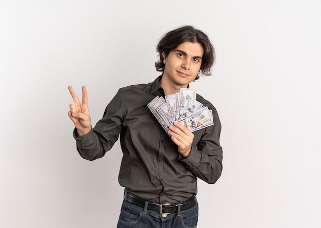 Junger selbstbewusster hübscher kaukasischer mann hält geld und gestikuliert siegeshandzeichen lokalisiert auf weißem hintergrund mit kopienraum