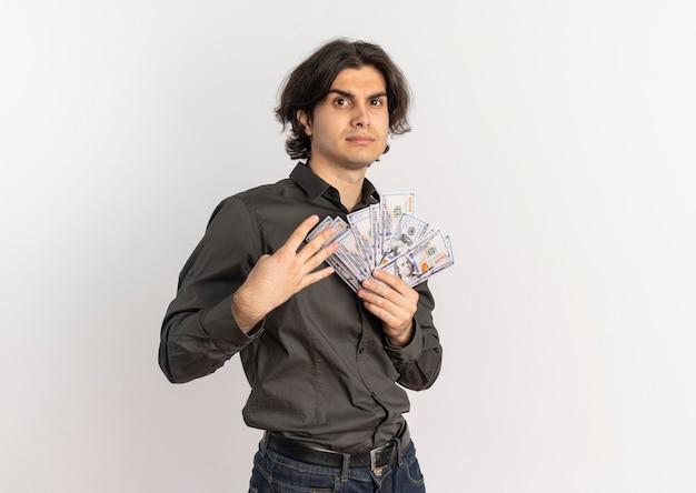 Junger selbstbewusster hübscher kaukasischer mann hält geld und gestikuliert vier mit den fingern lokalisiert auf weißem hintergrund mit kopienraum