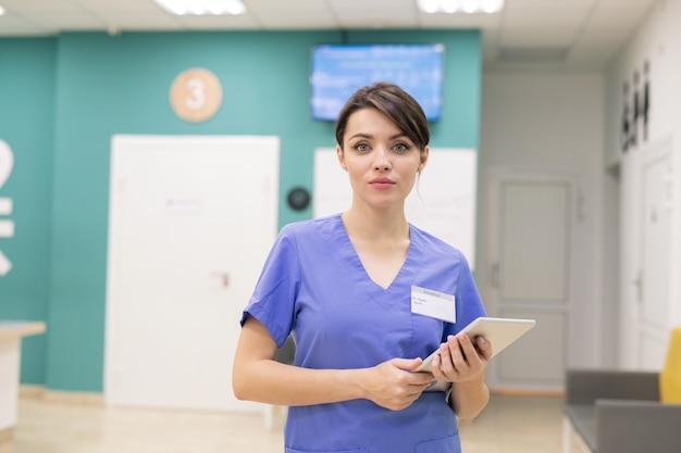 Junger selbstbewusster kliniker in uniform, der vor der kamera steht, während er touchpad verwendet, um patienten online zu konsultieren