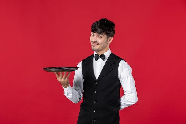 Junger selbstbewusster lächelnder mann kellner in einer uniform, der schmetterling am hals bindet, der tablett auf isoliertem rotem hintergrund hält