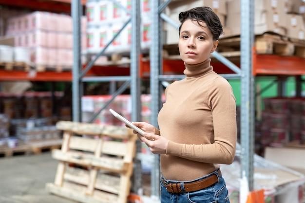 Junger selbstbewusster lagerarbeiter mit tablet steht gegen regale