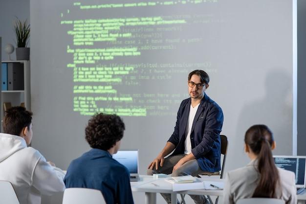Junger selbstbewusster lehrer, der seinen schülern informationen an bord erklärt und ihnen hilft, präsentationen für die konferenz zu machen