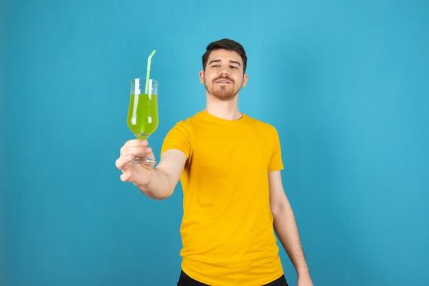 Junger selbstbewusster mann, der frischen grünen cocktail hält und ihn auf einem blau betrachtet.