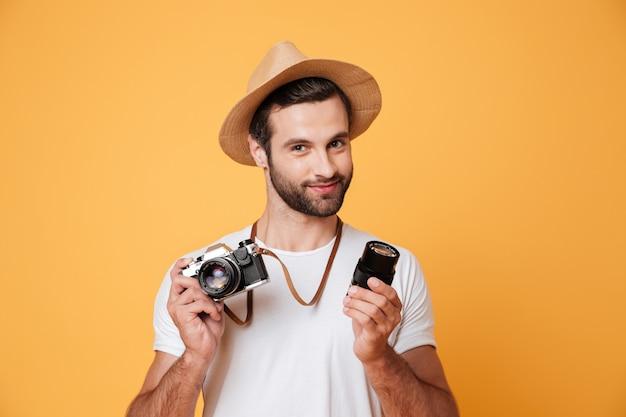 Junger selbstbewusster mann, der kamera und objektiv in den händen hält