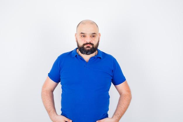 Junger selbstbewusster mann im blauen t-shirt