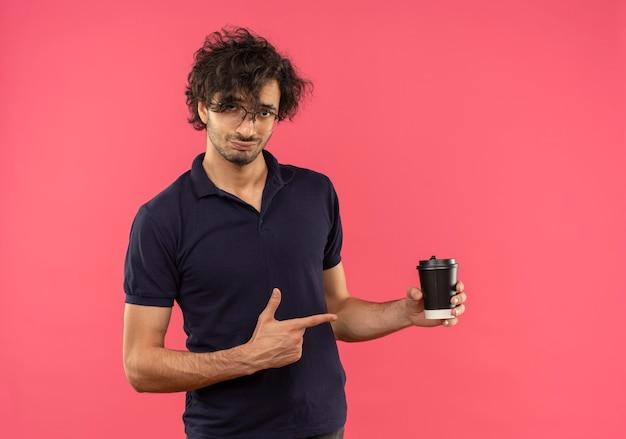 Junger selbstbewusster mann im schwarzen hemd mit optischen gläsern hält und zeigt auf kaffeetasse lokalisiert auf rosa wand