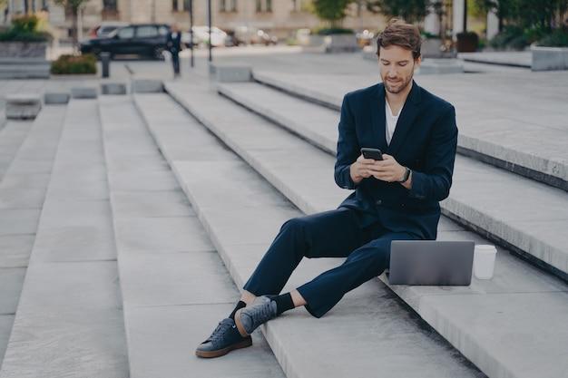 Junger selbstbewusster mann in stylischem anzug mit smartphone, während er mit laptop auf stufen draußen sitzt