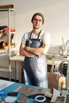 Junger selbstbewusster meister in brille und lederschürze verschränkt die arme auf der brust, während er in der werkstatt am tisch steht