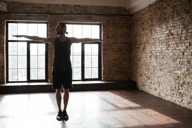 Junger selbstbewusster sportler, der sich im fitnessstudio aufwärmt