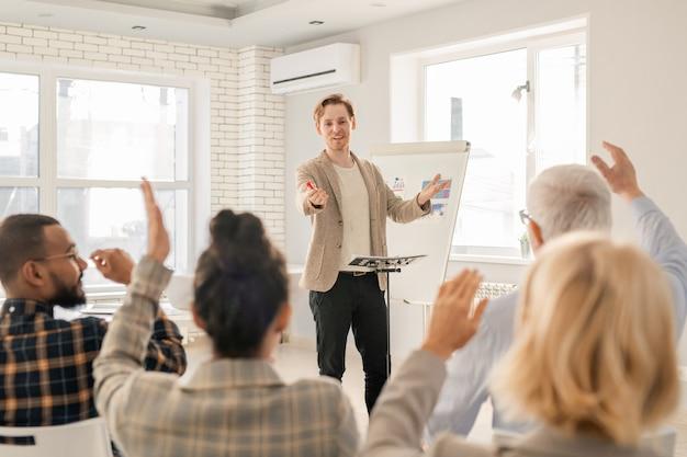 Junger selbstbewusster trainer, der einen seiner schüler mit erhobenen händen fragt, nachdem er die daten auf dem whiteboard erklärt hat