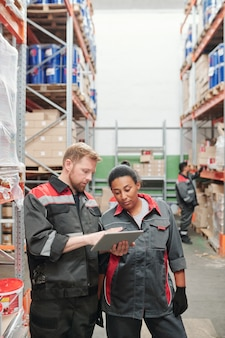 Junger selbstbewusster vorarbeiter oder lagerarbeiter mit tablet, während er seiner gemischtrassigen kollegin die liste der neuen waren zeigt