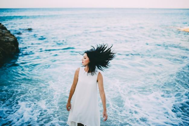 Junger sexy brunette im blauen wasser in einem weißen kleid am strand in griechenland