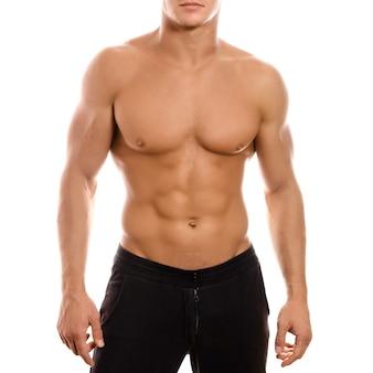 Junger sexy muskulöser machomann, der mit nacktem torso auf weißem hintergrund aufwirft