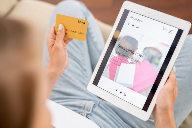 Junger shopaholic mit kreditkarte und digitalem tablet, der durch neue casualwear-kollektion im online-shop schaut