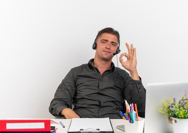 Junger sicherer blonder büroangestelltermann auf kopfhörern sitzt am schreibtisch mit bürowerkzeugen unter verwendung von laptop-gesten ok handzeichen, das kamera lokalisiert auf weißem hintergrund mit kopienraum betrachtet
