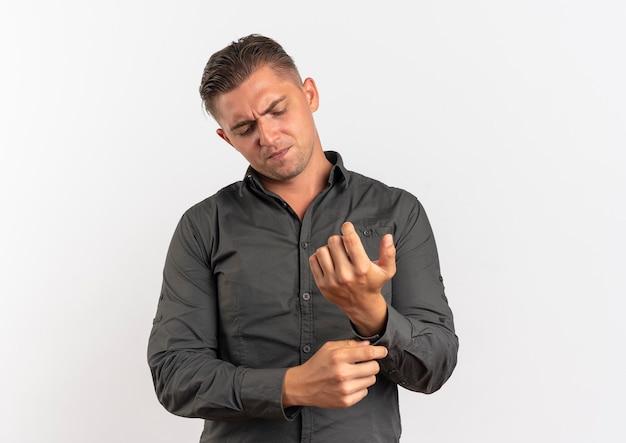 Junger sicherer blonder gutaussehender mann befestigt knopf auf seinem ärmel lokalisiert auf weißem hintergrund mit kopienraum