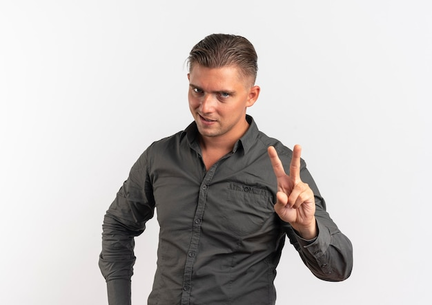 Junger sicherer blonder gutaussehender mann gestikuliert siegeshandzeichen lokalisiert auf weißem hintergrund mit kopienraum