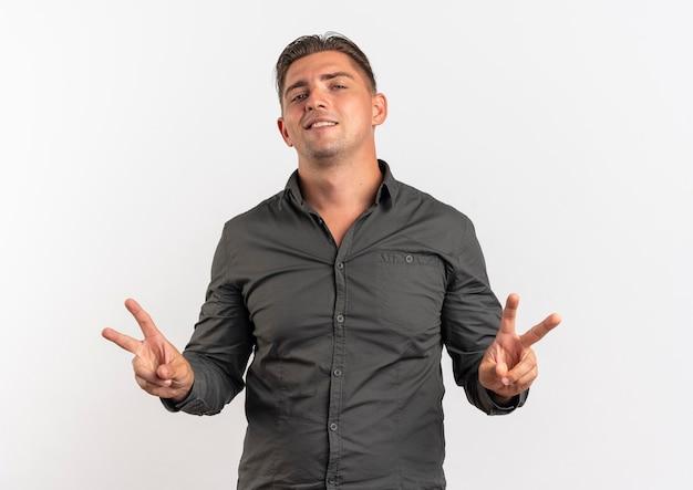 Junger sicherer blonder gutaussehender mann gestikuliert siegeshandzeichen mit beiden händen lokalisiert auf weißem hintergrund mit kopienraum