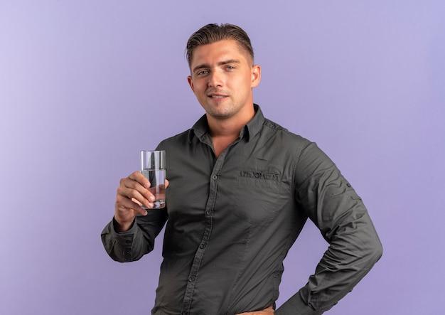 Junger sicherer blonder gutaussehender mann hält glas wasser isoliert auf violettem raum mit kopienraum