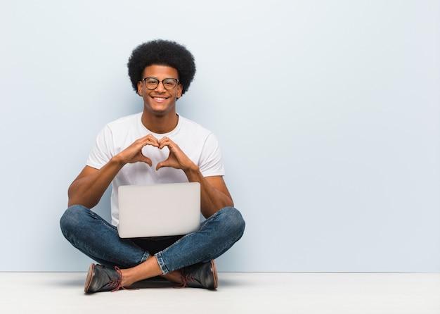 Junger sitzender boden des schwarzen mannes mit einem laptop, der eine herzform mit den händen tut