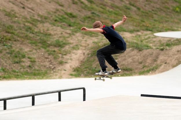 Junger skateboardathlet, der einen sprung in einem konkreten skatepark tut.