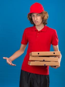 Junger skeptischer lieferbote in der roten uniform, die pizzaschachteln hält, die über lokalisierten blauen hintergrund verwirrt fühlen