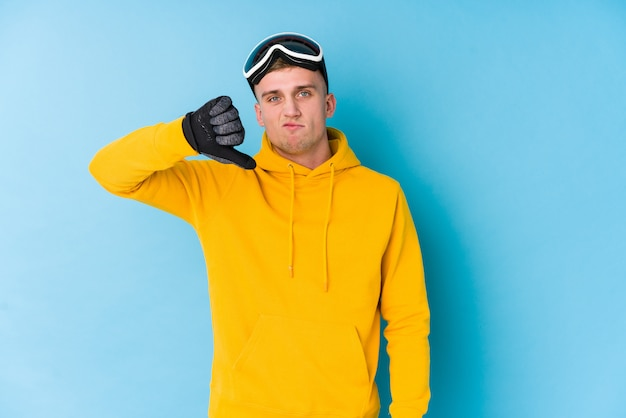 Junger skifahrermann, der eine abneigungsgeste, daumen unten zeigt. uneinigkeit konzept.
