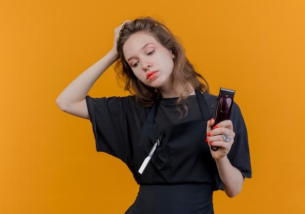 Junger slawischer weiblicher friseur, der uniform hält, die haarschneidemaschinen schaut, die hand auf kopf lokalisiert auf orange hintergrund setzen