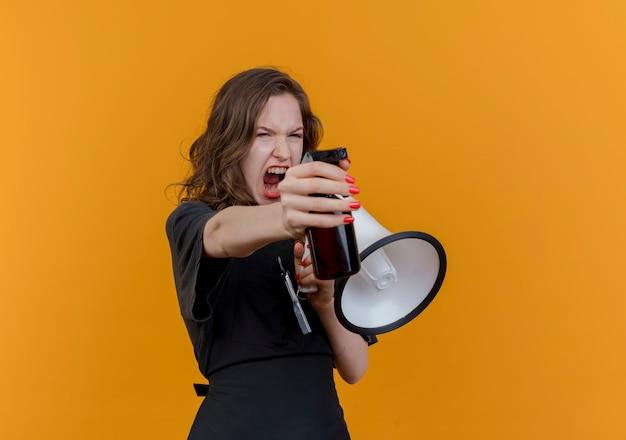 Junger slawischer weiblicher friseur, der uniform trägt, die im lautsprecher schreit und sprühflasche gerade lokalisiert auf orange hintergrund mit kopienraum sucht und ausdehnt