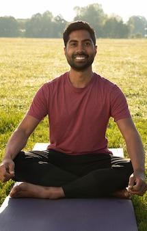 Junger smiley-mann, der draußen auf yogamatte meditiert