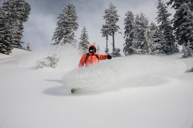 Junger snowboarder, der hinunter den schönen berg reitet