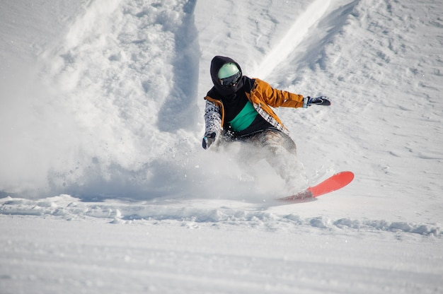 Junger snowboarder im bunten sportkleidungsreiten mit pulverschneehügel des snowboards unten