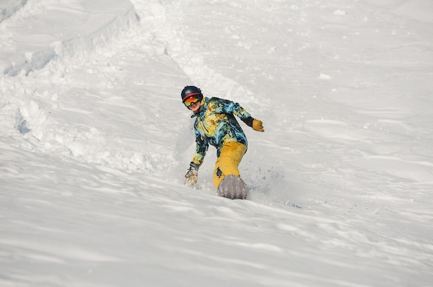 Junger snowboarder in der hellen sportbekleidung, die einen schneehügel am hellen wintertag hinunter reitet
