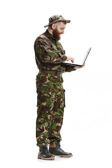 Junger soldat, der tarnuniform trägt, lokalisiert auf weißem studio
