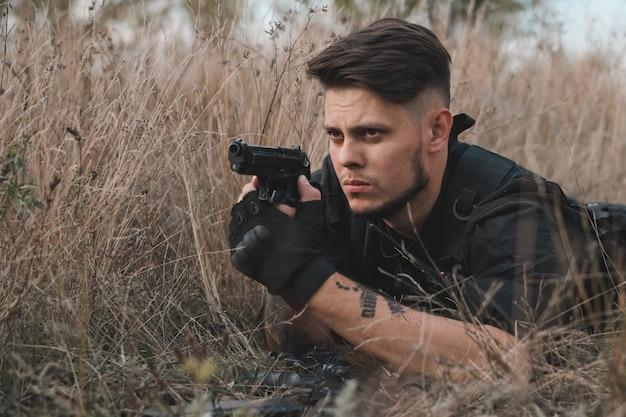 Junger soldat in schwarzer uniform, der sich hinlegt und eine pistole zielt