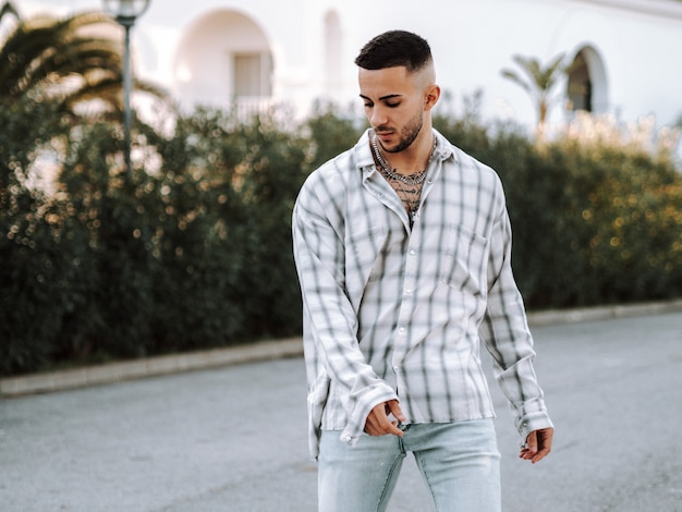 Junger spanier mit tattoos posiert auf der straße
