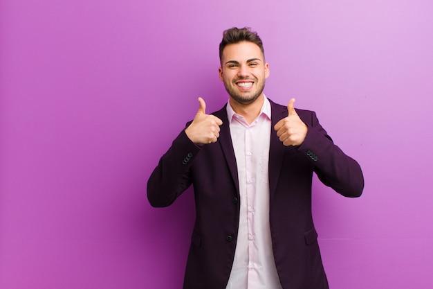Junger spanischer mann, der breit lächelnd glücklich, positiv, selbstbewusst und erfolgreich aussieht, mit beiden daumen nach oben