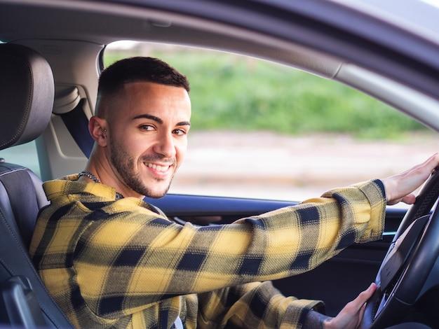 Junger spanischer mann, der ein auto lächelt und fährt