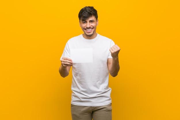Junger spanischer mann, der ein plakat hält, das sorglos und aufgeregt jubelt.