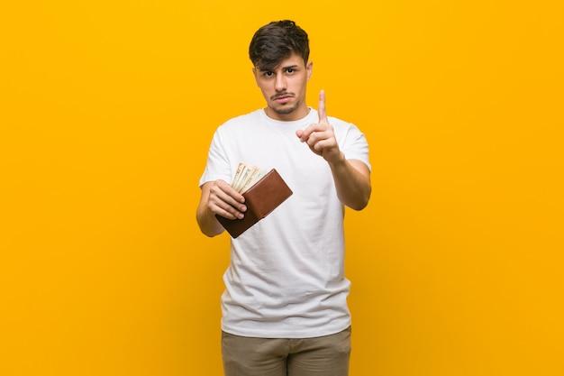 Junger spanischer mann, der eine brieftasche hält, die nummer eins mit finger zeigt.