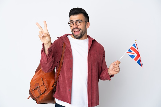 Junger spanischer mann, der eine flagge großbritanniens hält, die lächelt und siegeszeichen zeigt
