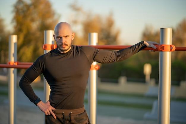 Junger spanischer mann, der eine pause nach dem training auf dem sportplatz hat