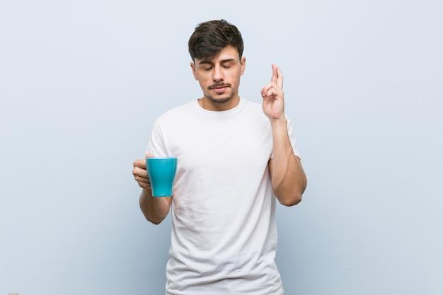 Junger spanischer mann, der eine tasse hält, die finger kreuzt, um glück zu haben