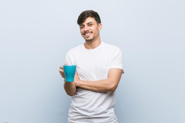 Junger spanischer mann, der eine tasse hält, die mit verschränkten armen selbstbewusst lächelt.