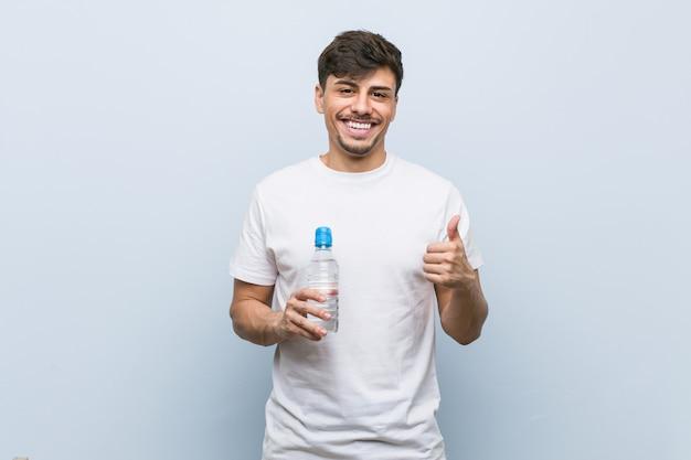 Junger spanischer mann, der eine wasserflasche hält, die lächelt und daumen hochhebt