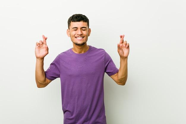 Junger spanischer mann, der finger kreuzt, um glück zu haben