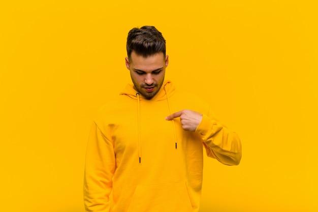 Junger spanischer mann, der fröhlich und beiläufig lächelt, nach unten schaut und auf brust gegen orange wand zeigt